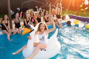 Frau sitzt auf einem aufblasbaren Schwan in einem Pool und weitere Frauen jubeln sitzen am Rand des Pools.