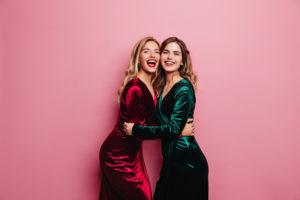 Zwei Frauen umarmen sich und schauen dabei in die Kamera.