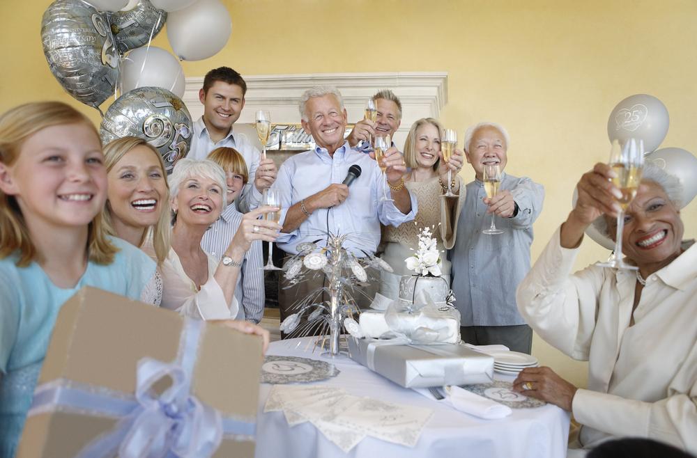 Eine Menschengruppe ist um einen älteren Mann versammelt und heben ein Sektglas.