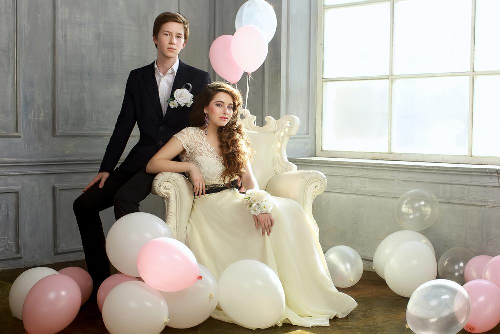 Zwei Jugendliche, Mädchen und Junge; sitzen auf einem Stuhl und sind von Luftballons umgeben.