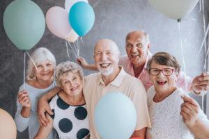 5 Senioren stehen mit Luftballons in den Händen und lächeln