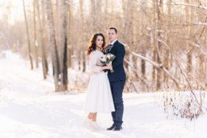 Brautpaar steht umarmend im Schnee