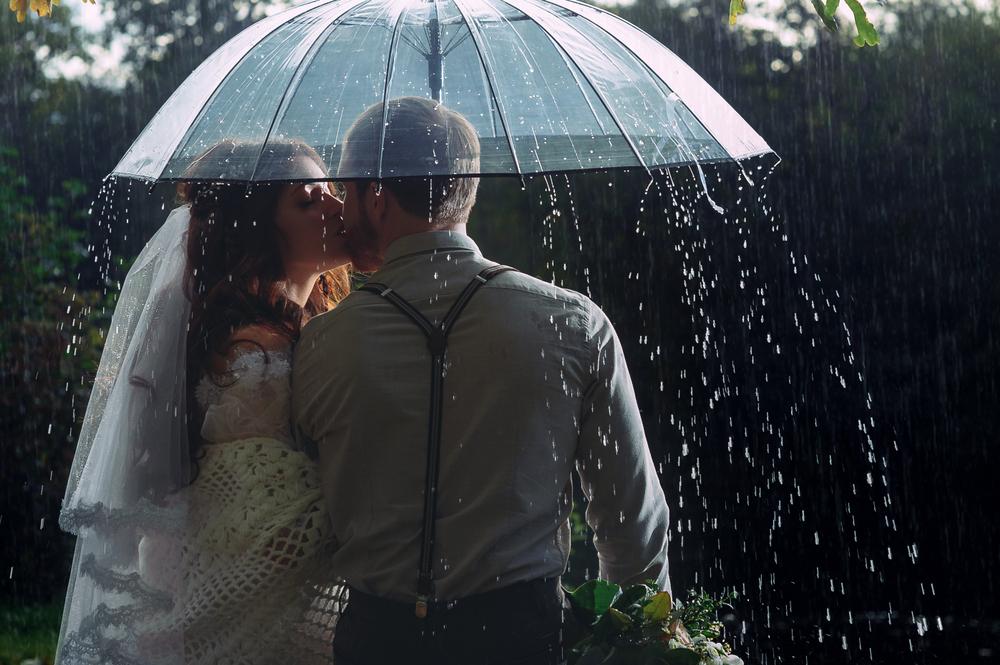 Brautpaar küsst sich unter einem transparenten Regenschirm.
