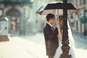Brautpaar steht im strömenden Regen unter einem Regenschirm und schaut sich in die Augen.