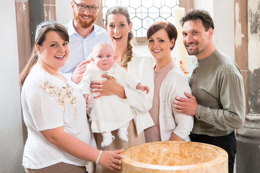 Eltern und Geistige stehen bei der Taufe mit dem Kind in einer Kirche
