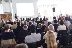 Redner, der bei einer geschäftlichen Veranstaltung im Konferenzsaal spricht