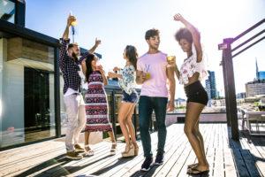 Multiethnische Gruppe von Freunden, die auf dem Dach feiern