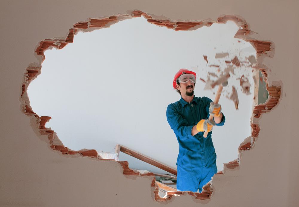 Mann reisst Wand  mit einem Hammer ein
