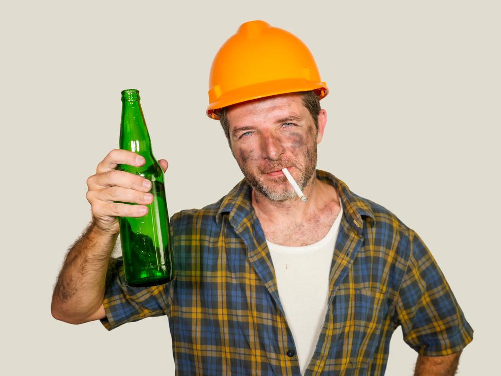 Mann hält eine Flasche hoch und raucht dabei eine Zigarette