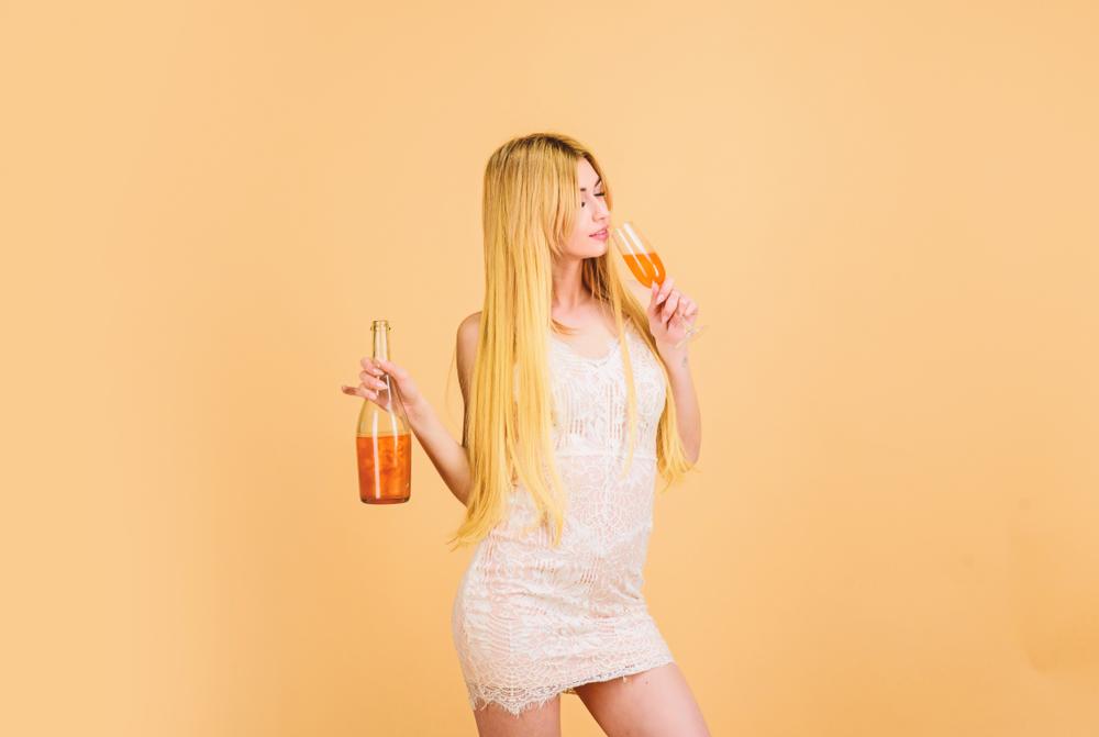 Frau trinkt Sekt und hält eine Sektflasche in der rechten Hand.