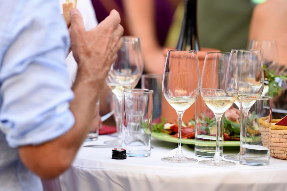 Einige Weingläser auf einem Stehtisch im Sommer