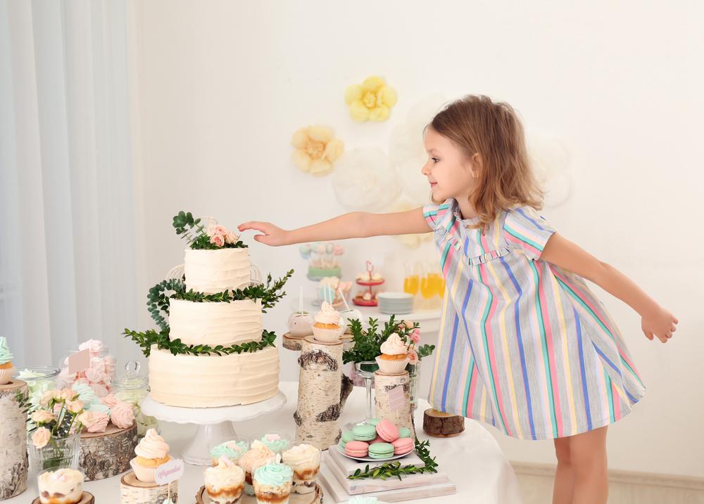 Mädchen steht vor einer Candy Bar und streckt ihre rechte Hand gen einer drei-stöckigen Torte.