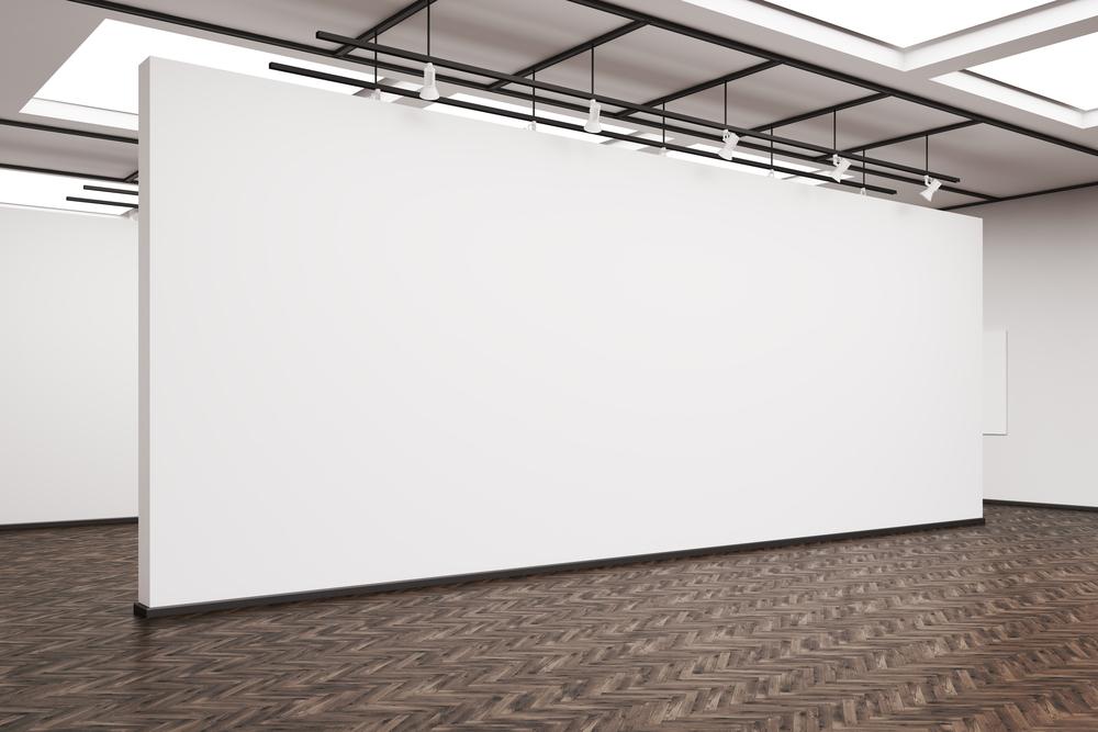 Seitenansicht einer großen weißen Wand in einer Kunstgalerie.