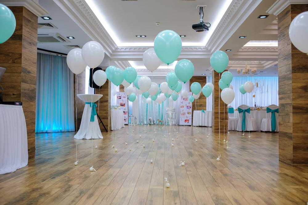 Aussicht auf ein leeres Studio-Restaurant mit weißen und türkisfarbenen Ballons auf einer Tauffeier.